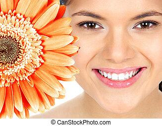 Schöne Frau lächelt mit Blumen.