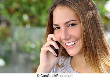 Schöne Frau mit einem perfekten weißen Lächeln, die auf dem Handy spricht.