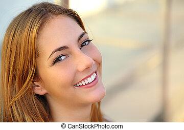 Schöne Frau mit einem perfekten weißen Lächeln und glatter Haut.