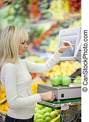 Schöne junge Frau kauft Obst und Gemüse in der Gemüseabteilung eines Lebensmittelladens/Supermarkts