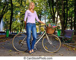 Schöne junge Frau mit Fahrrad im Herbstpark.