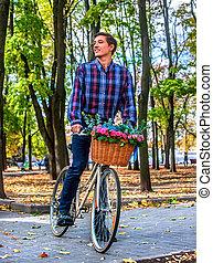Schöne junge Frau mit Fahrrad im Park.