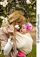 Schöne junge Mutter mit ihrer kleinen Tochter in einem Garten im Frühling.