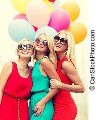 Schöne Mädchen mit bunten Ballons in der Stadt.