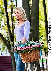 Schöne romantische junge Frau auf dem Fahrrad im Park.
