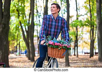 Schöner junger Mann mit Fahrrad im Park.
