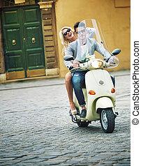 Schöner Mann, der mit seiner Freundin einen Roller fährt.
