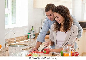 Schöner Mann, der mit seiner Freundin kocht.