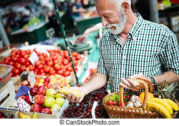 Schöner Senior-Mann, der frisches Obst und Gemüse auf einem Markt kauft.