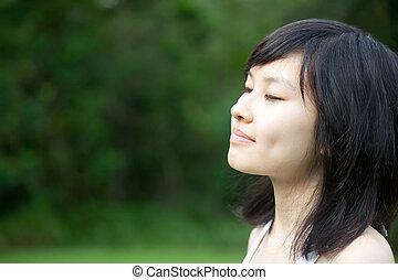 Schönes asiatisches Mädchen, das die Natur genießt