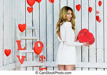 Schönes, glückliches Mädchen mit einer Herz-Geschenkbox