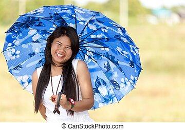 Schönes junges Thai-Mädchen unter einem blauen Sonnenschirm.