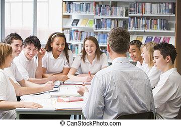 Schüler und Lehrer in einer Lerngruppe, die zusammenarbeiten