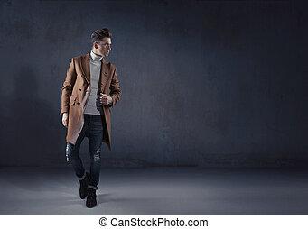 Schlauer, stilvoller Kerl mit einem Herbstmantel.