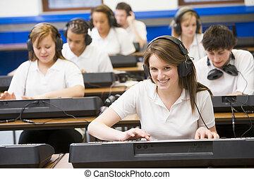Schulkinder üben an einer Tastatur im Musikunterricht