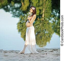 Schwangere Dame, die am Strand spazieren geht.