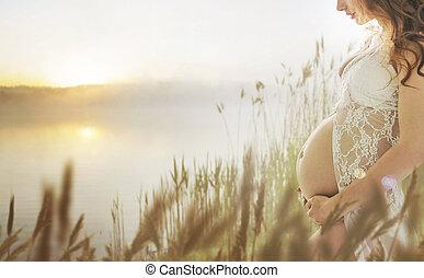 Schwangere Dame, die auf der frischen Sommerwiese läuft.