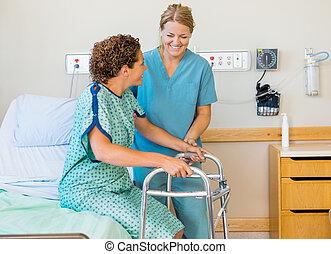 Schwester assistiert Patienten mit Hilfe von Laufrahmen im Krankenhaus.
