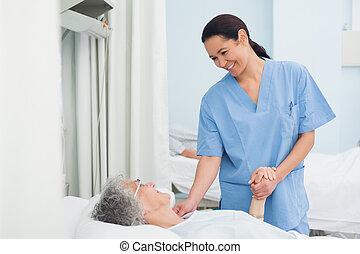 Schwester hält die Hand eines Patienten