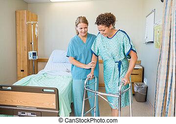 Schwester hilft Patienten, mit Walker im Krankenhaus zu laufen.