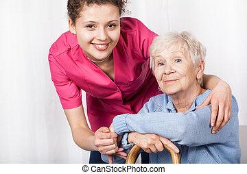 Schwester mit sitzender, alter Frau.