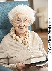 Senior Frau, die sich im Bücherregal auf dem Stuhl entspannt.