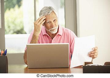 Senior Mann benutzt Laptop zu Hause