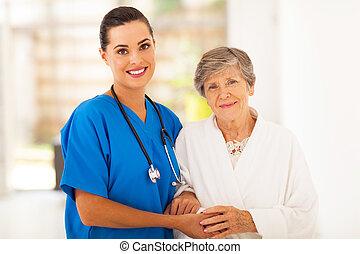Seniorin und fürsorgliche junge Krankenschwester