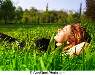 Serene Frau entspannt sich draußen in frischem Gras