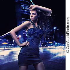 Sexy junge Schönheit, die über Nacht im Hintergrund posiert