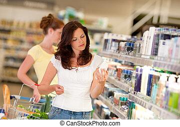 Shopping-Serie - Braune Haarfrau in Kosmetikabteilung.