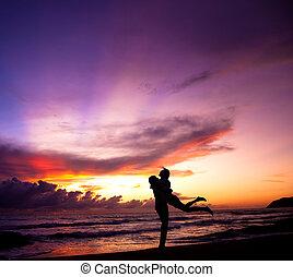Silhouette des glücklichen Paares, das sich am Strand umarmt