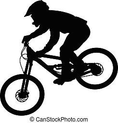Silhouette eines Radfahrers, der auf einem Mountainbike auf einer Piste runterfährt.