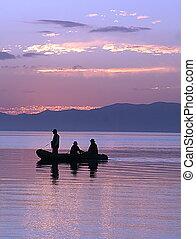 Silhouette von drei Männern in einem Boot.