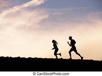 Silhouette von Mann und Frau, die zusammen in den Sonnenuntergang joggen, Wellness Fitness-Konzept