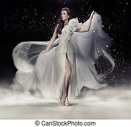 Sinnliche Brünette, die in weißem Kleid tanzt.