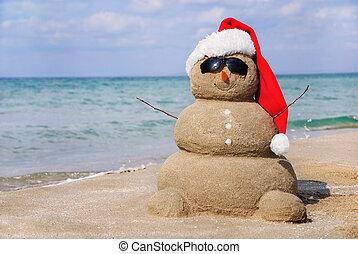 Snowman aus Sand. Urlaubskonzept kann für neues Jahr und Weihnachtskarten verwendet werden