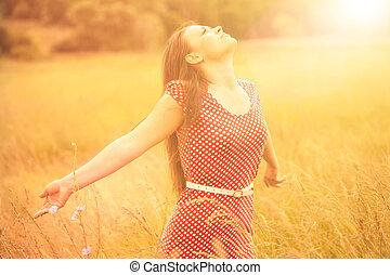 Sommerspaß. Junge glückliche Frau, die Sonnenlicht auf der Weizenwiese genießt