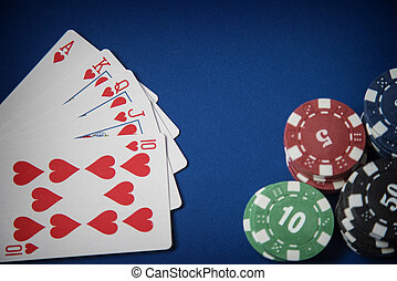 Spielchips und Royal Flush Poker Hand auf blauem Filz Hintergrund.