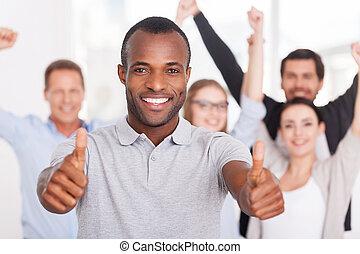 stehende , tragen, seine, gruppe, geschäftsmenschen, auf, ausstellung, junger, sie, team., während, daumen, hintergrund, afrikanisch, lächelnden mann, beiläufig, glücklich