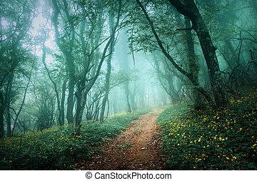 Straße durch einen geheimnisvollen dunklen Wald im Nebel mit grünen Blättern a