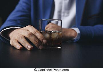 Stressiger Geschäftsmann mit einem Glas Whiskey, den er schläft und Data Charts, Geschäftsdokument am Bürotisch. Alkoholsucht - betrunkenes Geschäftsmann-Konzept