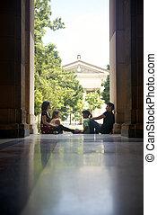 Studenten an der Universität, eine Gruppe junger Männer und Frauen, die reden