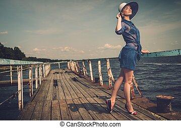 Stylishe Frau mit weißem Hut steht auf dem alten Holzpier