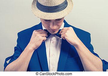 Stylisher Kerl mit Hut und blauen Jackenkleidern Schmetterling.