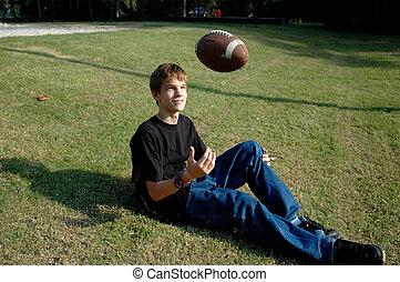 Teen berührt Football.