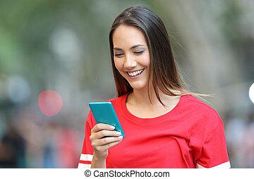 Teen in Rot mit einem blauen Smartphone auf der Straße.