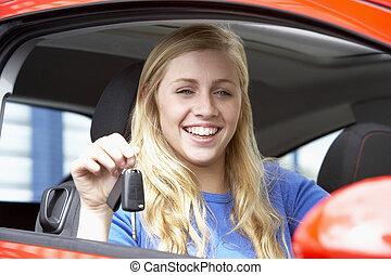 Teenage-Mädchen sitzt im Auto, hält Autoschlüssel und lächelt die Kamera an.
