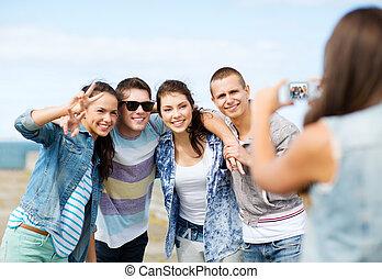 Teenager, die draußen Fotos machen