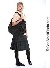 Teenagerin in Schuluniform und Schultertasche